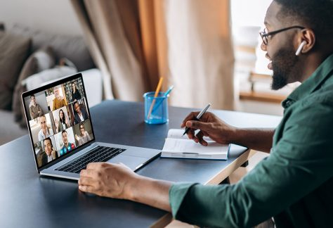 A man sat at home at a desk with his laptop. The man is on a virtual meeting