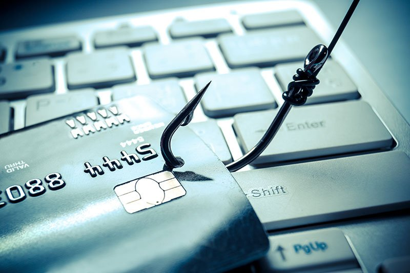 A hook on a credit card laid over a computer keyboard